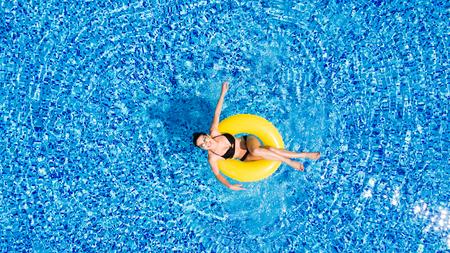 水泳プールの膨脹可能な大きな yellpw に若いブルネットの女性の空撮。彼女の休日のリラックスしたスリムな女性の平面図です。 写真素材