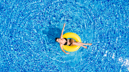 Aerial view of young brunette woman swimming on the inflatable big yellpw in the pool. Top view of slim lady relaxing on her holidays.