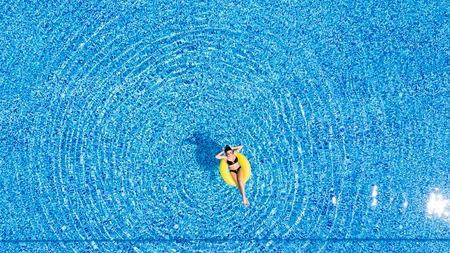 Aerial of young brunette woman swimming on the inflatable big yellow ring in pool Stock Photo