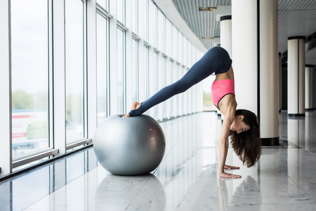Young woman doing exercises with fit ball at gym. Woman is doing fitness at home on room floor near the window. Stok Fotoğraf - 79747789