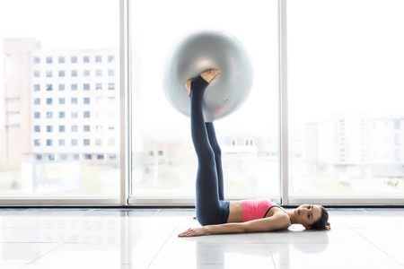 Woman working out with exercise ball in gym. Pilates woman doing exercises in the gym workout room with fitness ball.