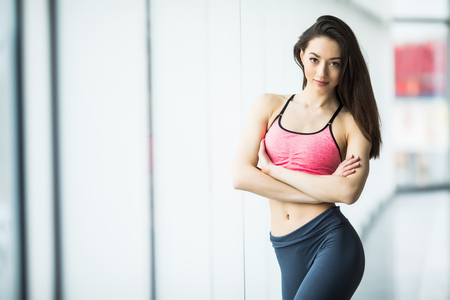 Young woman resting after workout at gym. Fitness female taking break after training session in health club. Фото со стока