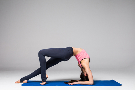 Young attractive woman practicing yoga, standing in different yoga exercise, wearing sportswear isolated on grey background. Yoga position concept