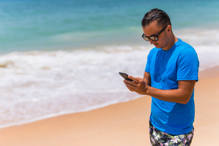 Man use phone on the beach typing or use internet on sunny day . Summer time