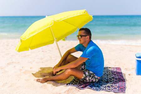 Lazing man in sun under solar umbrella on towel enjoy the lazy time on the beach. Summer time Stock Photo