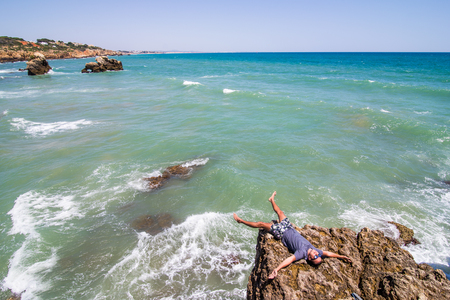 Young man lying  on the rocks cliffs  over the ocean of algarve portugal Stock Photo