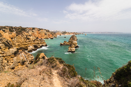 Travel to stunning rocks cliffs with seas caves on sandy camilo beach in colorful sunny blue sky. Summer vocation.