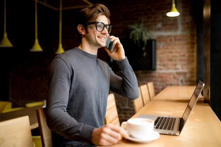 メガネでは、ハンサムな若いフリーランス話すラップトップの中のスマート フォン 写真素材