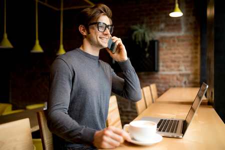 Handsome young freelancer in eye glasses speak smartphone while on laptop