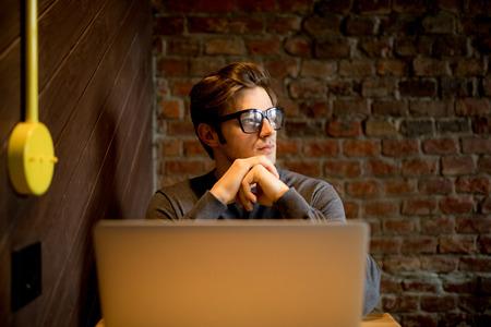 Close up portrait of mindful male blogger in eyewear watching  in windowac