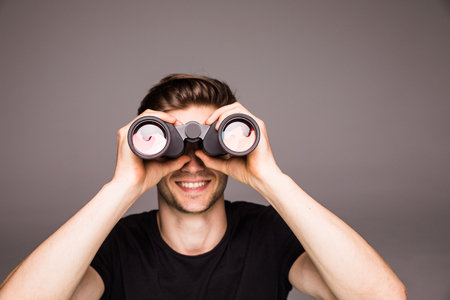 Young handsome man searching with binoculars near laptop at office work place