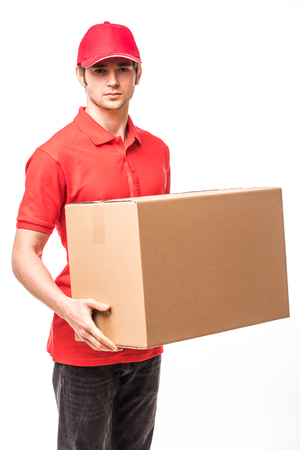 Cheerful delivery man happy young courier holding a cardboard box and smiling while standing on white