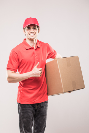 Delivery man in red uniform with thumbs up with box in hands isolated on white back Stock Photo