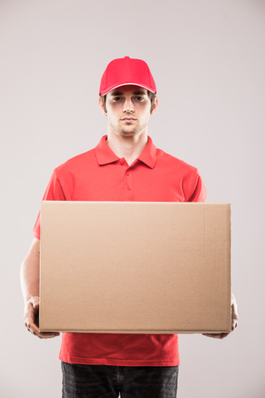 Cheerful delivery man happy young courier holding a cardboard box and smiling while standing Reklamní fotografie