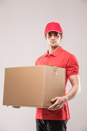 Cheerful delivery man happy young courier holding a cardboard box and smiling while standing Reklamní fotografie - 82612889