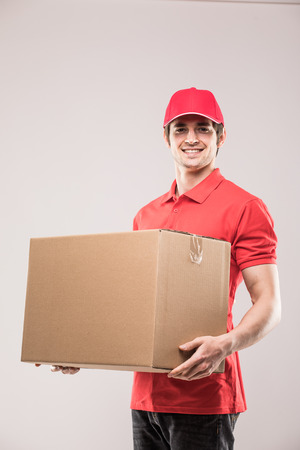carrying: Cheerful delivery man happy young courier holding a cardboard box and smiling while standing Stock Photo