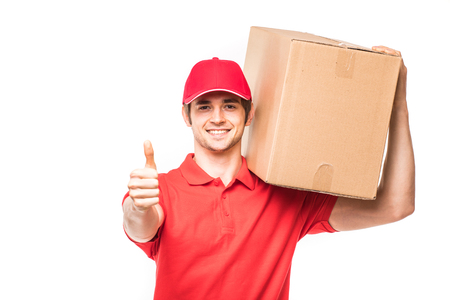 Mover man showing thumb up and smiling standing near cardboard boxes isolated on white background