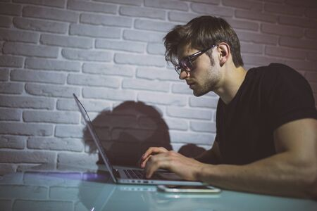Handsome young programmer working at home late in evening. Hacker
