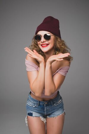Stylish night flash fashion portrait of trendy casual young woman in sunglasses and hat smile in studio Stock Photo