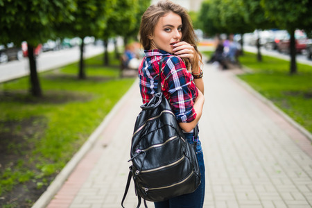 Fashion portrait trendy young woman with backpack in the city summer