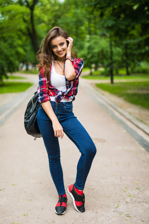 Student girl walking down the street with a backpack in the park Stock Photo