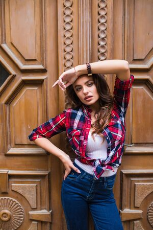 portrait of smiling woman on a background of brown vintage door wearing casual clothes in summer city