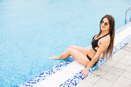 Woman sitting on the edge of swimming pool.