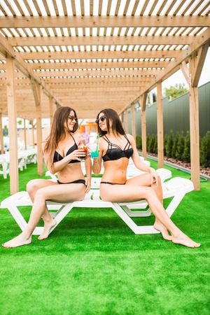 Two beautiful women having cocktails together by the swimming pool