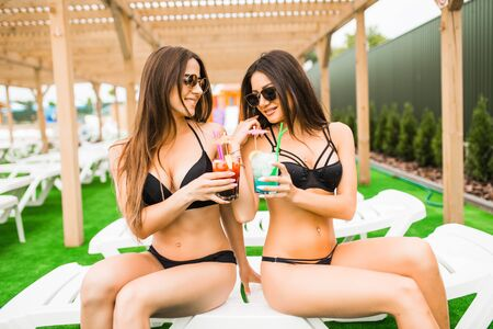 Let the vacation begin Two beautiful women having cocktails together by the swimming pool Stock Photo