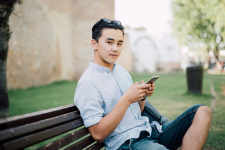 Young fashionable man sitting on the bench in the park with phone in his hands