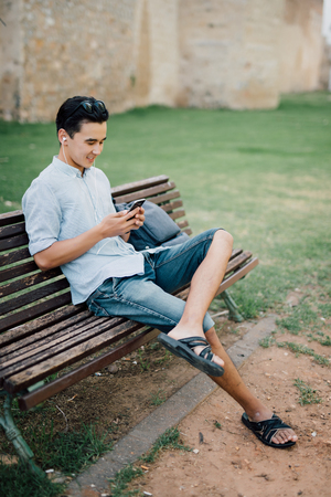 Profile of a happy guy using a smart phone sitting on a bench in a park