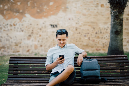 Profile of a happy guy using a smart phone sitting on a bench in a park Stock fotó - 82823708