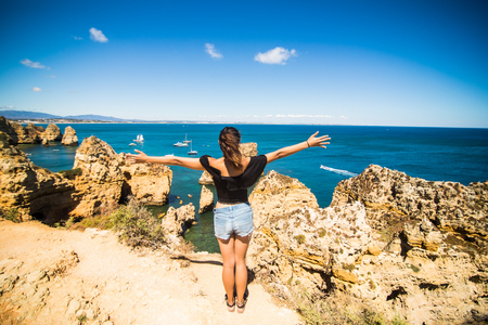 woman bath: Beautiful latin woman standing on a rock above the ocean and welcomes Stock Photo
