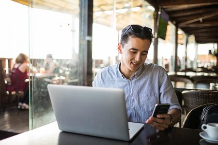電話カジュアルな専門家によってソーシャル メディア アプリケーションの若いアジア ビジネス男テキスト メッセージ