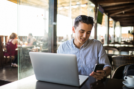 Young asian business man texting message on social media application by phone casual professional