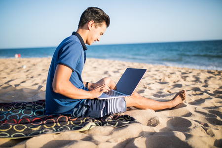 Young asian man working with laptop computer on tropical beach Stock Photo - 82990228
