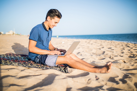 アジア青年トロピカルビーチでラップトップ コンピューターを操作