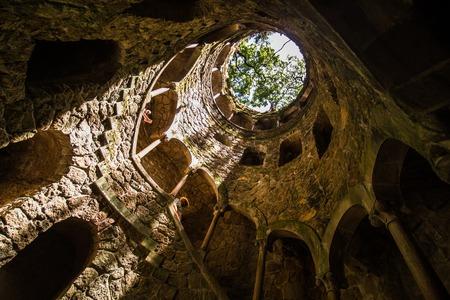 Sintra에있는 Quinta da Regaleira의 시작 우물. 우물의 깊이는 27 미터입니다. 그것은 지하 통로를 통해 다른 터널과 연결됩니다.