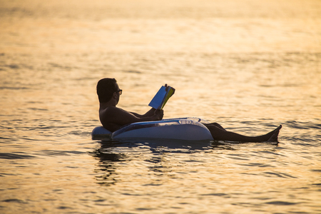 Young man in relax in the ocean water on inflatable ring on sunset read a book. Summer vocation