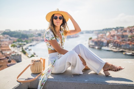 Young woman sitting on the view point in front of the Douro river and Dom luis I bridge in Porto, Portugal. Stock Photo