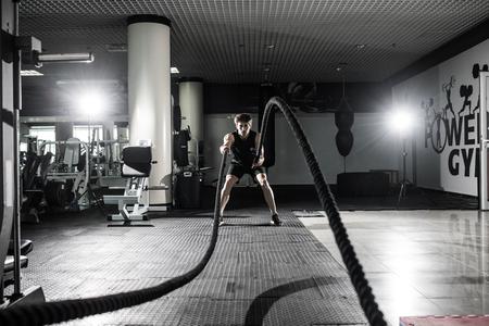 피트 니스 체육관에서 전투 밧줄 전투 로프 운동 남자. CrossFit.