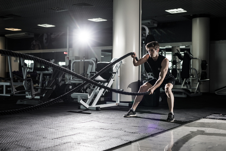 Crossfit battling ropes at gym workout exercise Foto de archivo