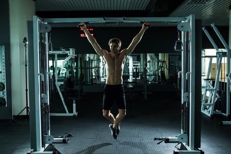 very power athletic guy , execute exercise tightening on horizontal bar, in sport-hall, glamour light, look stare on camera