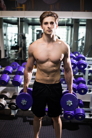 very power athletic guy , execute exercise with dumbbells, in gym Stock Photo