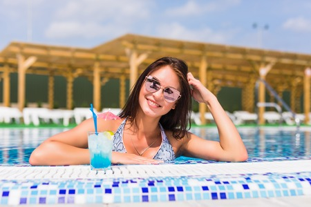 portrait of young sexy girl relaxing at the edge of the swimming pool., wearing swimsuit and drinking cocktails during vacation.