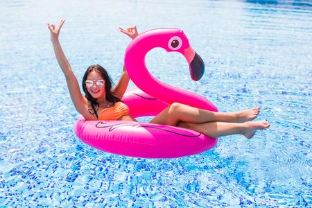 座っている女の子がプールで膨脹可能なマットレスのフラミンゴ