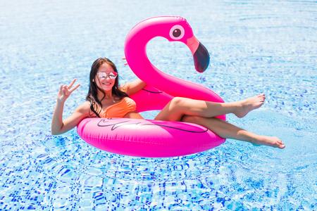 Jeune et sexy fille s'amuser et rire sur un matelas de flotteur de piscine flamant rose gonflable géant dans un bikini. Jolie femme bronzée se trouve au soleil en vacances Banque d'images
