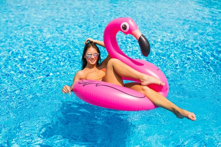 Enjoying vacation girl with sunglasses in the swimming pool.