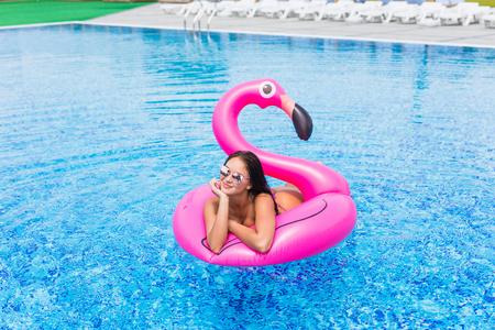 Het portret van de manier van een jong en sexy meisje in de pool op een opblaasbare roze flamingo in een badpak en zonnebril Stockfoto