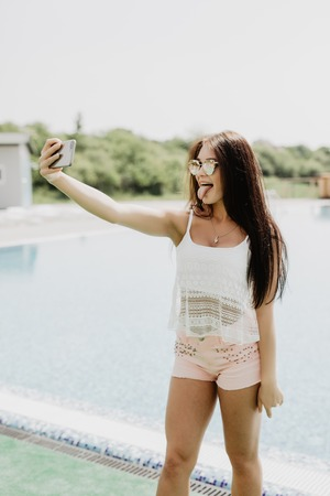 Close-up selfie-portrait of attractive brunette girl with long hair standing near pool. She wears pink T-shirt, sunglasses.